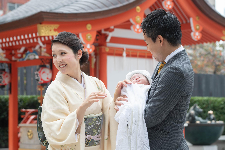 赤ちゃんを抱くスーツ姿の男性と横に立つ和装の女性