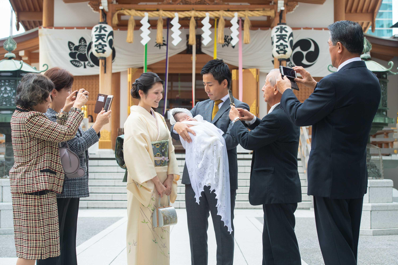 赤ちゃんを抱くスーツ姿の男性と横に立つ和装の女性を携帯のカメラで撮影する複数の人