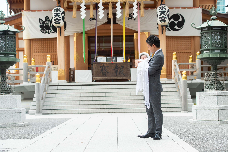 赤ちゃんを抱くスーツ姿の男性