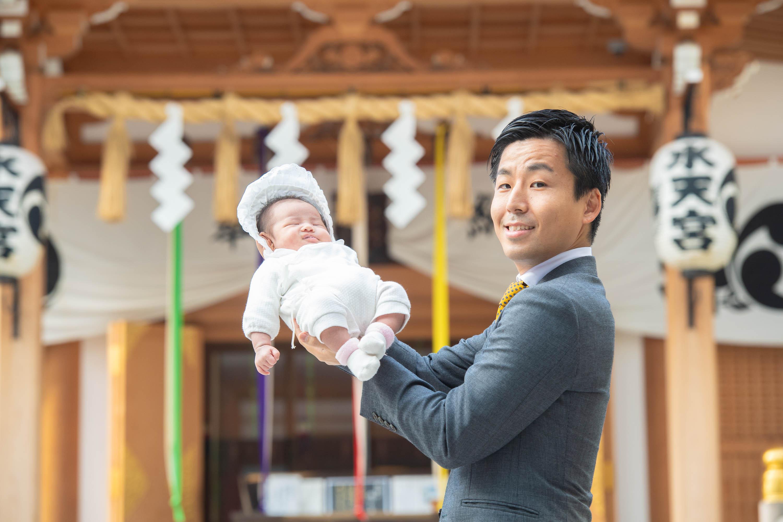 赤ちゃんを手で持ち上げ抱くスーツ姿の男性