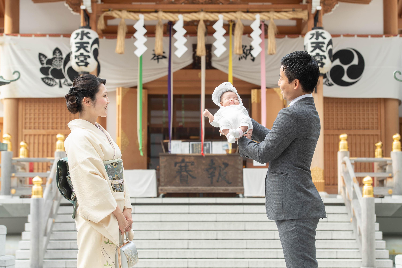 赤ちゃんを手で持ち上げ抱くスーツ姿の男性と横に立つ和装の女性