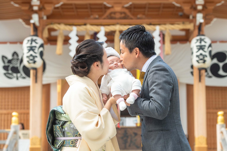 赤ちゃんを手で持ち上げキスをするスーツ姿の男性と横に立つ和装の女性