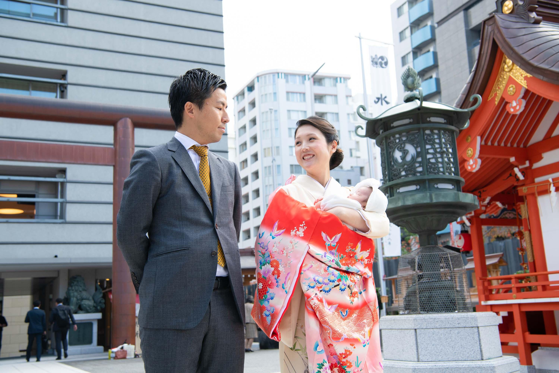 お宮参りの赤い掛着を着て立つ女性とスーツ姿の男性