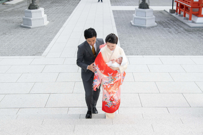 水天宮本殿の前の階段をのぼる赤ちゃんを抱いた女性と男性