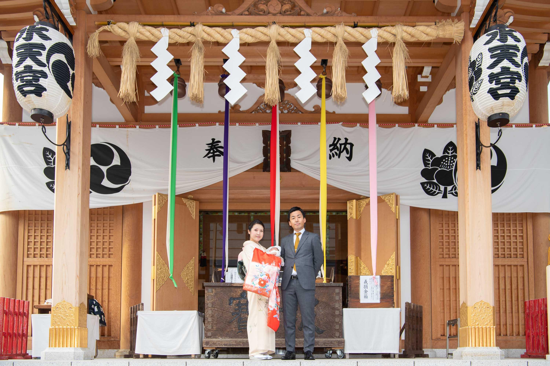 水天宮本殿の下に立つお宮参りの掛着を着た和装の女性と横に立つスーツ姿の男性