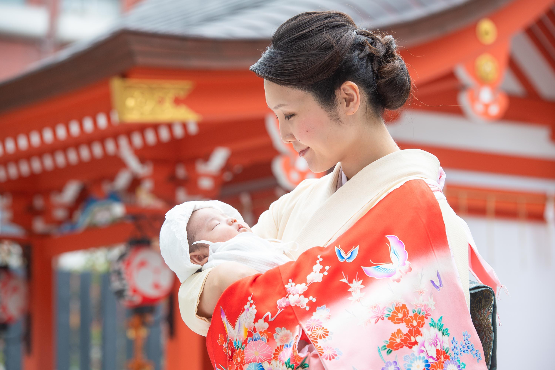 掛着を着た和装の女性に抱かれる赤ちゃん