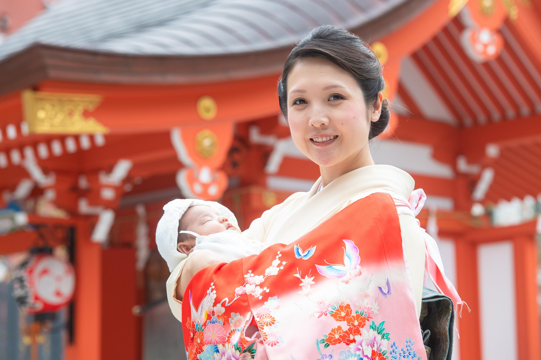 掛着を着てこちらを見る和装の女性に抱かれる赤ちゃん