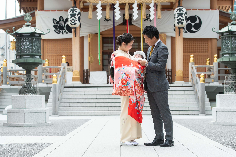 掛着を着た和装の女性に抱かれる赤ちゃんと横にいるスーツ姿の男性