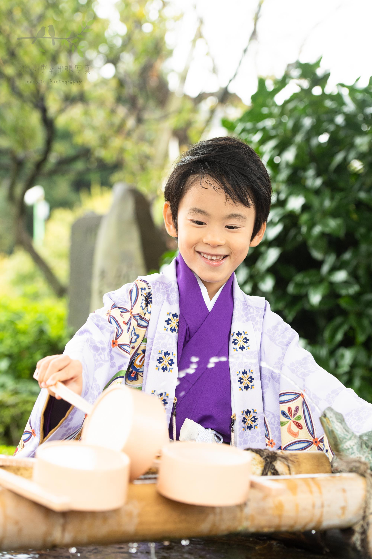 手水舎のひしゃくで水をすくおうとしている七五三の紫色の着物姿の男の子