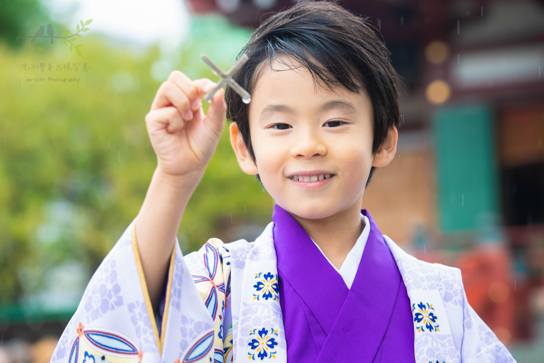 ポーズを取る紫色の着物姿の七五三の男の子