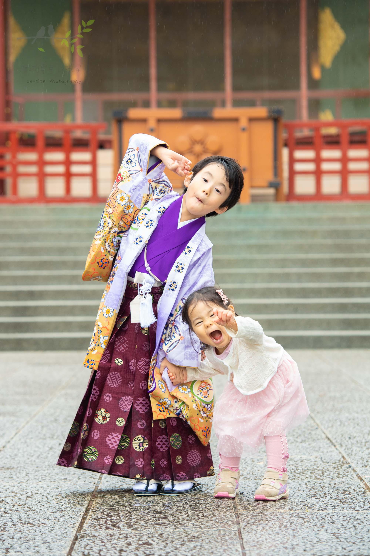 ポーズを取る紫色の着物姿の男の子と小さな女の子