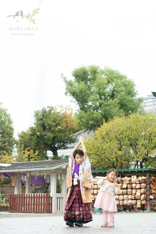 立っている紫色の着物姿の男の子と小さな女の子