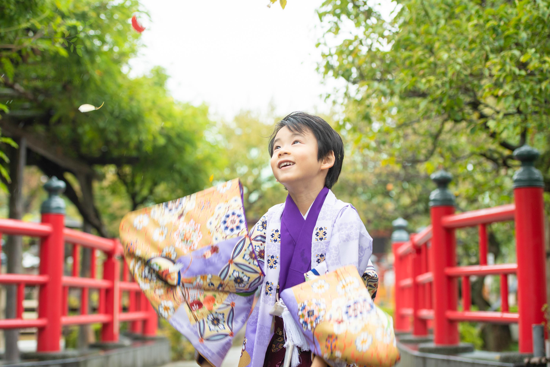 葉っぱを上に投げる紫色の着物姿の七五三の男の子
