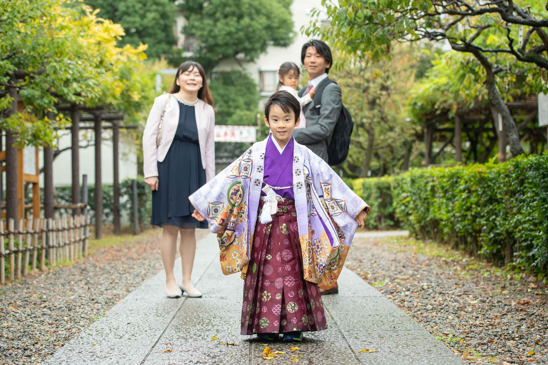 立っている紫色の着物姿の七五三の男の子と後ろに立つ家族