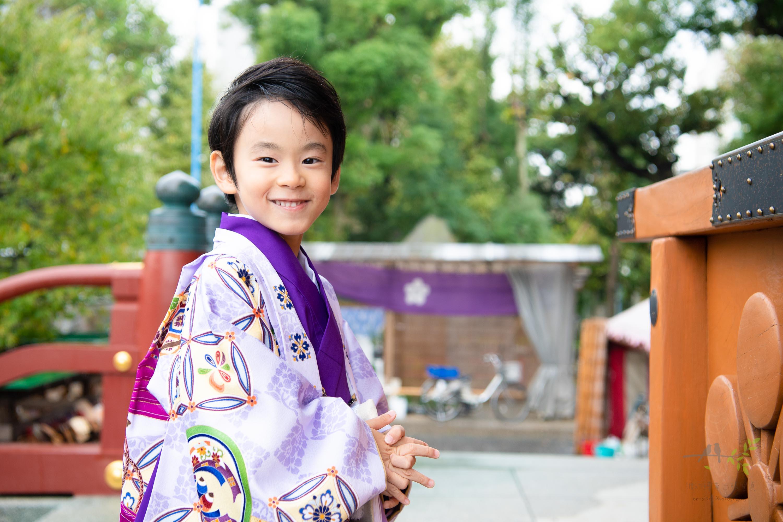 お祈りをする紫色の着物姿の男の子