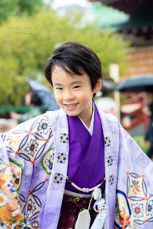 七五三の紫色の着物姿で微笑む男の子