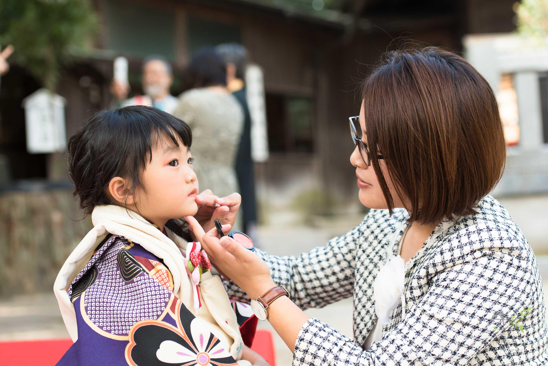 七五三の着物姿で口紅を直している小さな女の子とママ