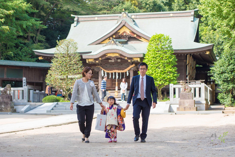 七五三の着物姿で手をひかれ歩く小さな女の子とママとパパ