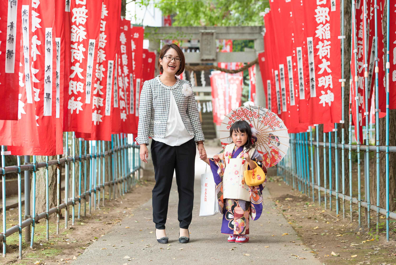 赤い神社のぼりの参道に立つ小さな和傘をさした七五三の着物姿の女の子と女性