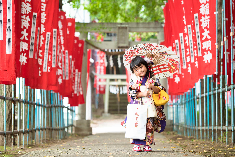 赤い神社のぼりの参道に立ち小さい和傘を持つ七五三の着物姿の女の子