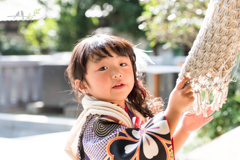 神社の鈴を鳴らしている女の子