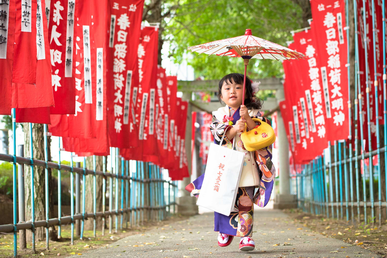 赤い神社のぼりの参道で和傘を持ち走ってくる七五三の着物姿の女の子
