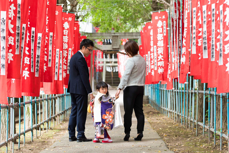 赤い神社のぼりの参道で手を引かれ歩く七五三の着物姿の女の子