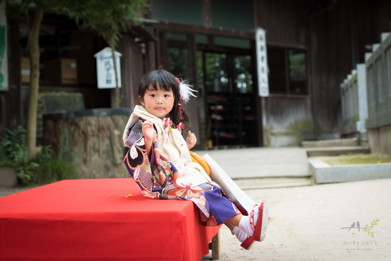 赤色の縁台に座る着物姿の七五三の女の子