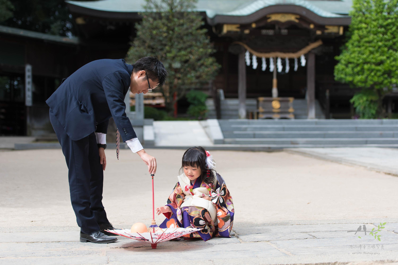 小さな和傘で遊ぶ着物姿の女の子と男性