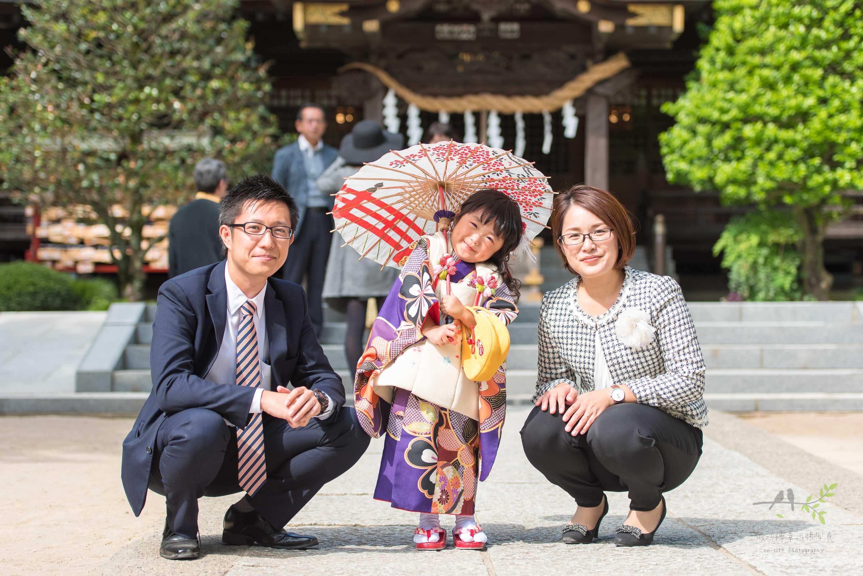 七五三の着物姿で和傘を指す小さな女の子と横にしゃがむママとパパ