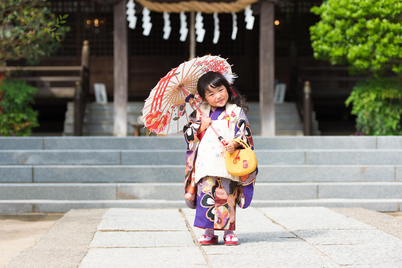 七五三の着物姿で和傘を指す小さな女の子