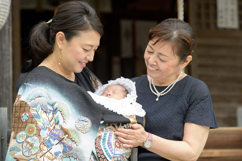 掛着姿の赤ちゃんを抱っこした女性と横に寄り添う女性