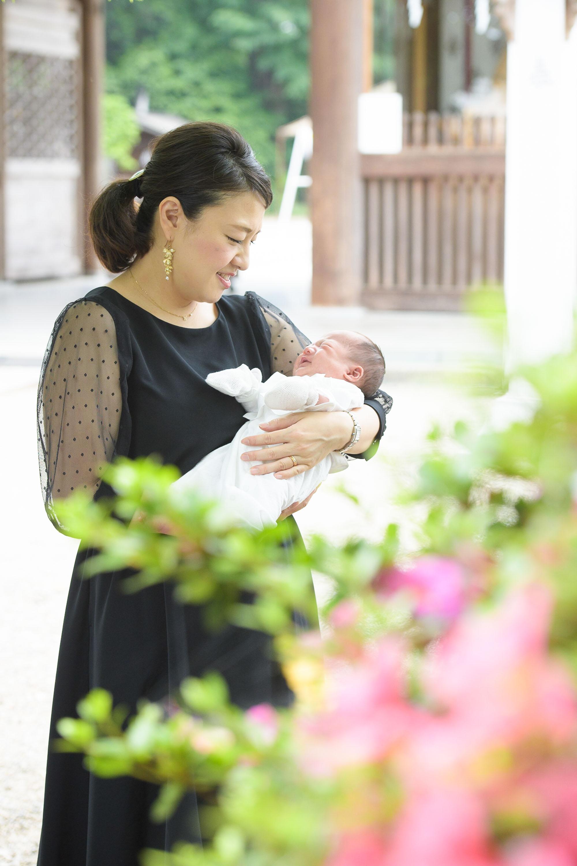 植栽越しに赤ちゃんを抱っこする女性