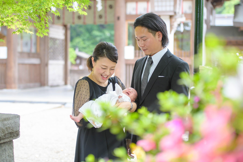 植栽越しに赤ちゃんを抱っこする笑顔の女性と男性