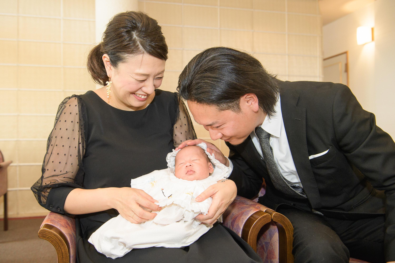 白いベビードレスに身を包んだ赤ちゃんを抱く女性と顔を寄せる男性