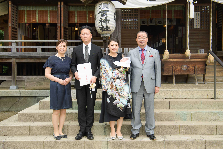 須賀神社の本殿の前に立つお宮参りの4人家族