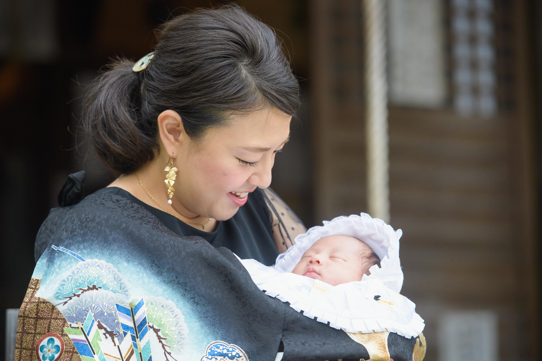 お宮参りの掛着姿の女性と抱っこされた赤ちゃん