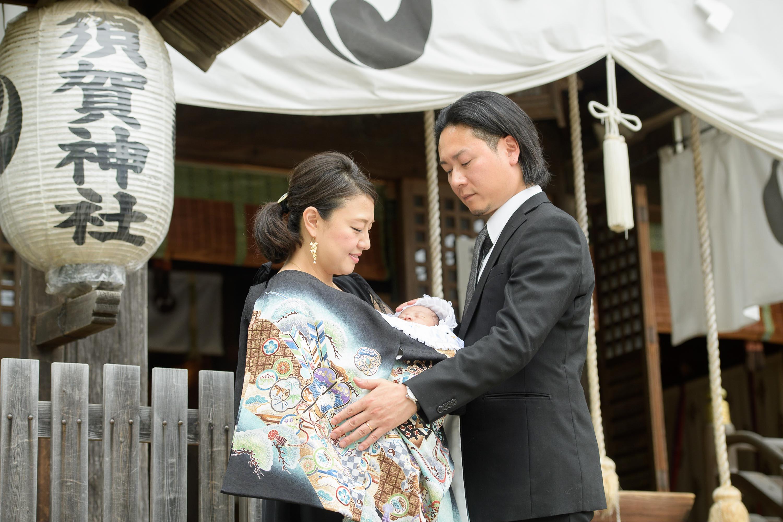 お宮参りの掛着姿の女性と抱っこされた赤ちゃんと横に立つ男性