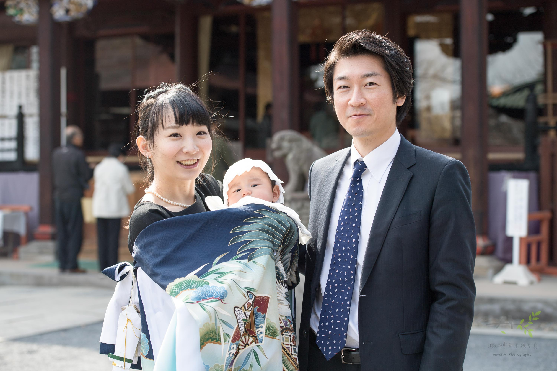 掛着を着て赤ちゃんを抱っこする女性と横に立つ男性