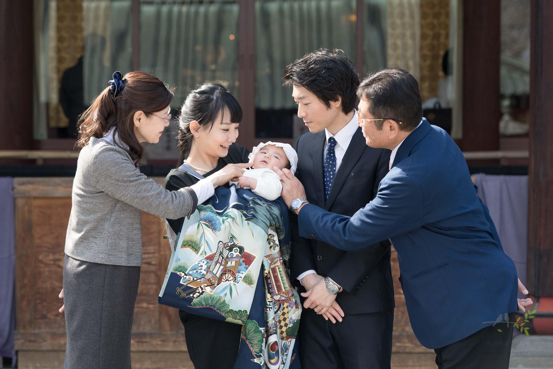 掛着を着た女性が抱っこする赤ちゃんの頬を触る3人