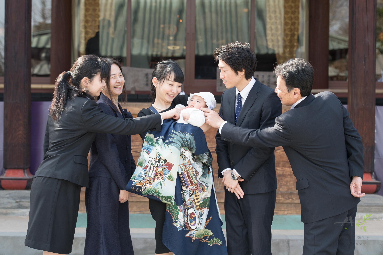 掛着を着た女性が抱っこする赤ちゃんの頬を触る4人