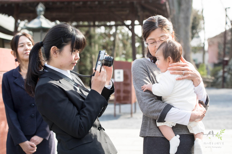 メガネをかけた女性が抱く赤ちゃんの写真を撮る女性