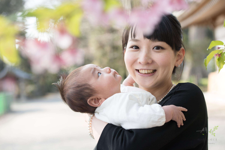 桜の花の下の女性と赤ちゃん