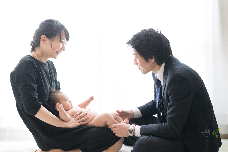 裸の赤ちゃんを抱く女性と足を持つ男性