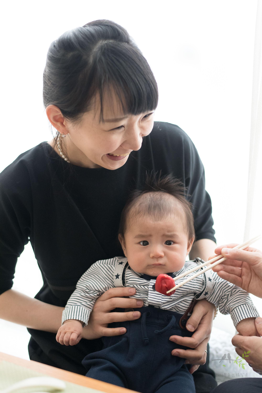 梅干しが口元に寄せられた赤ちゃんを抱き笑う女性