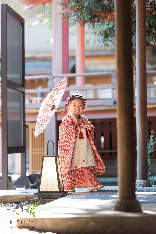 小さな和傘を指して歩く七五三の女の子