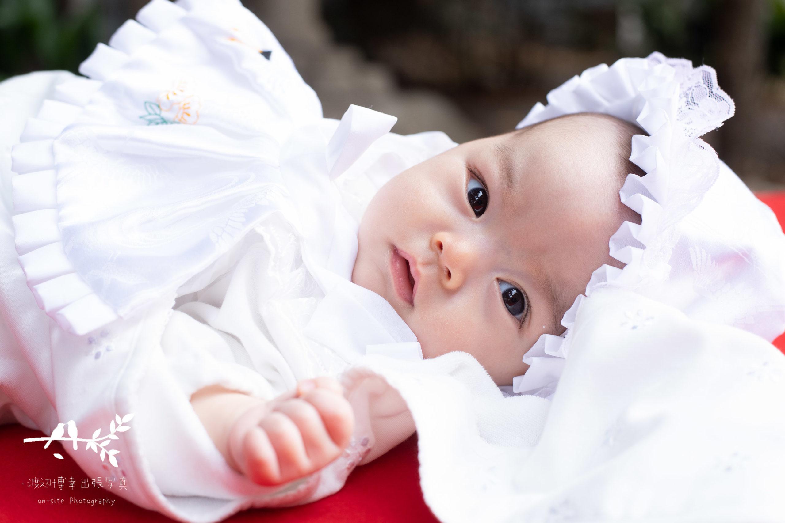 ベビードレスを着た赤ちゃんがこちらを見て