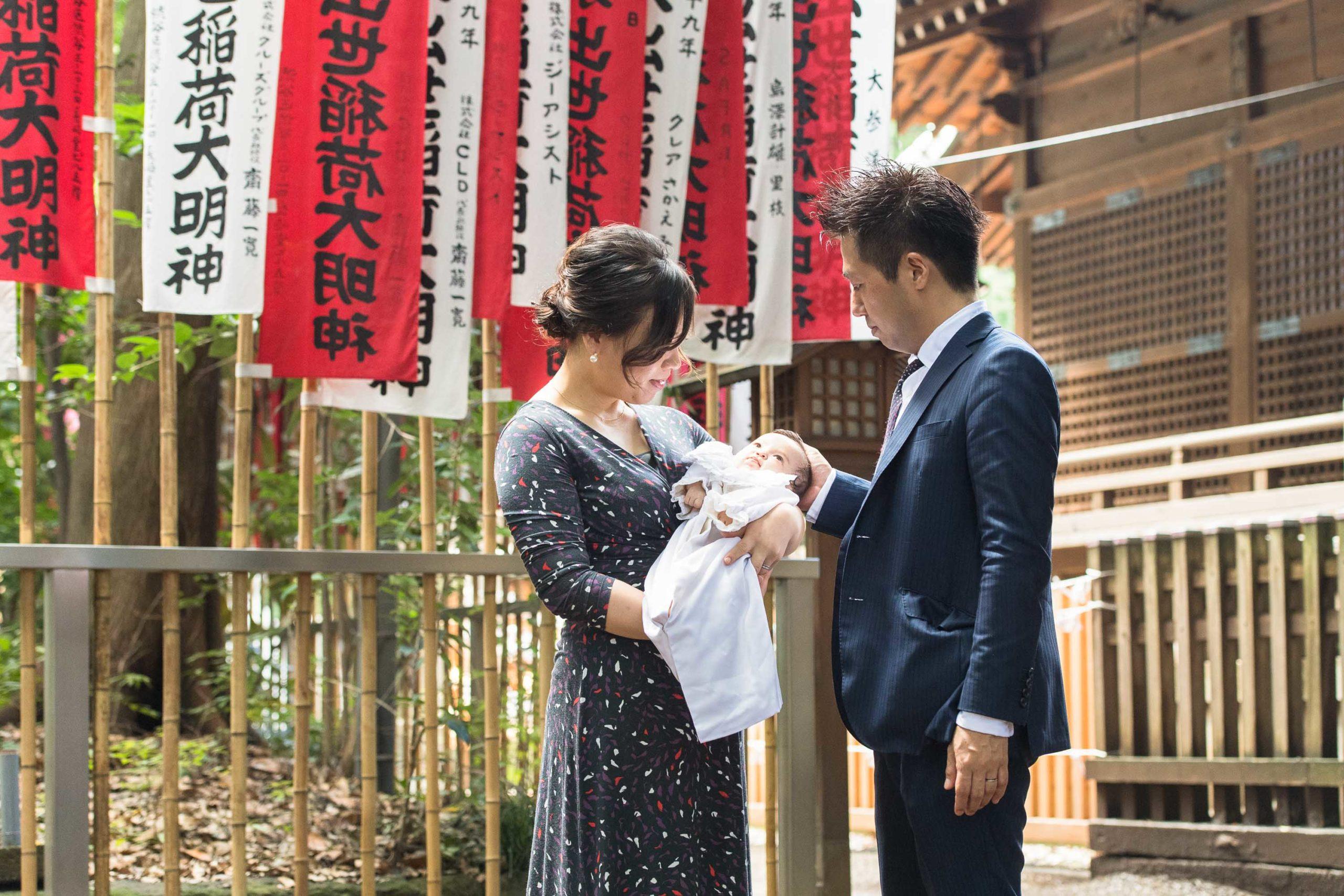 神社旗の前で赤ちゃんを抱く女性と横に立つ男性