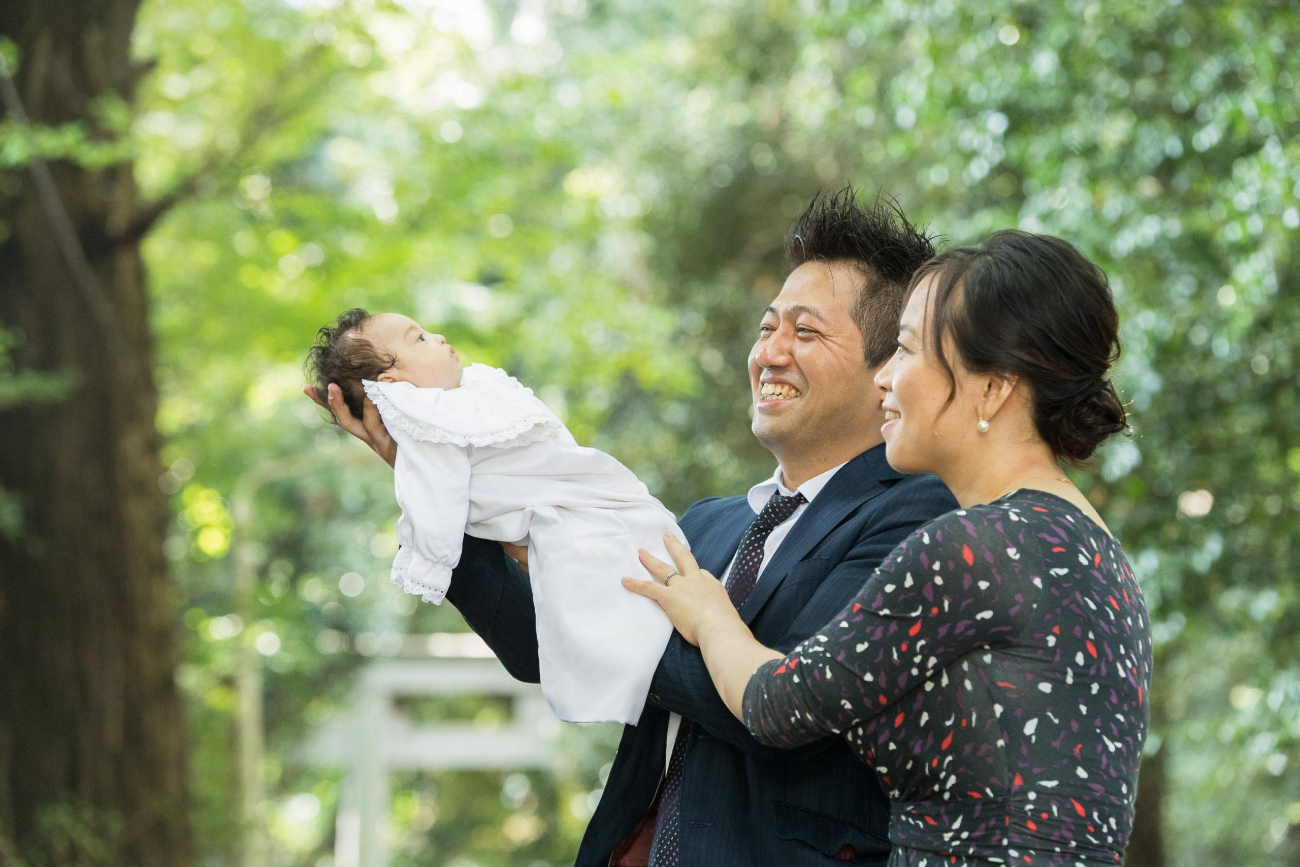 ライオンキングのように赤ちゃんを高く上げる男性と横に立つ女声