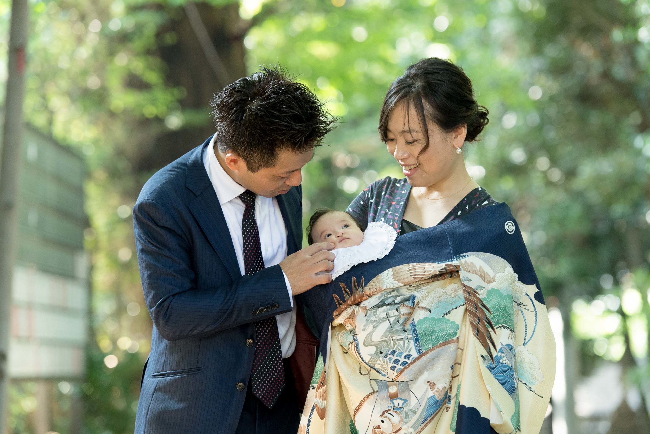 初着で赤ちゃんを抱く女性と横に立つ男性
